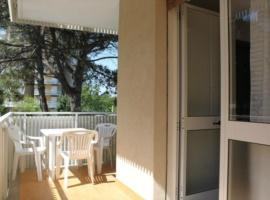 Apartment mit Balkon und ein Sonnenschirm am Strand mit zwei Liegen
